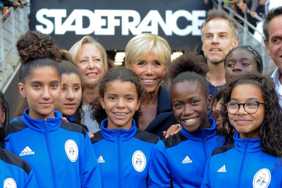 Brigitte Macron très contente de prendre la pose avec les jeunes filles du club de Saint-Denis