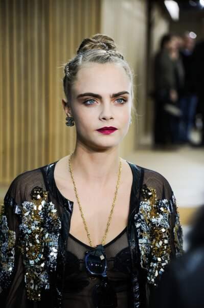 et parée d'un superbe beauty look: rouge à lèvres lie-de-vin, smoky eye cuivré et tresses plaquées