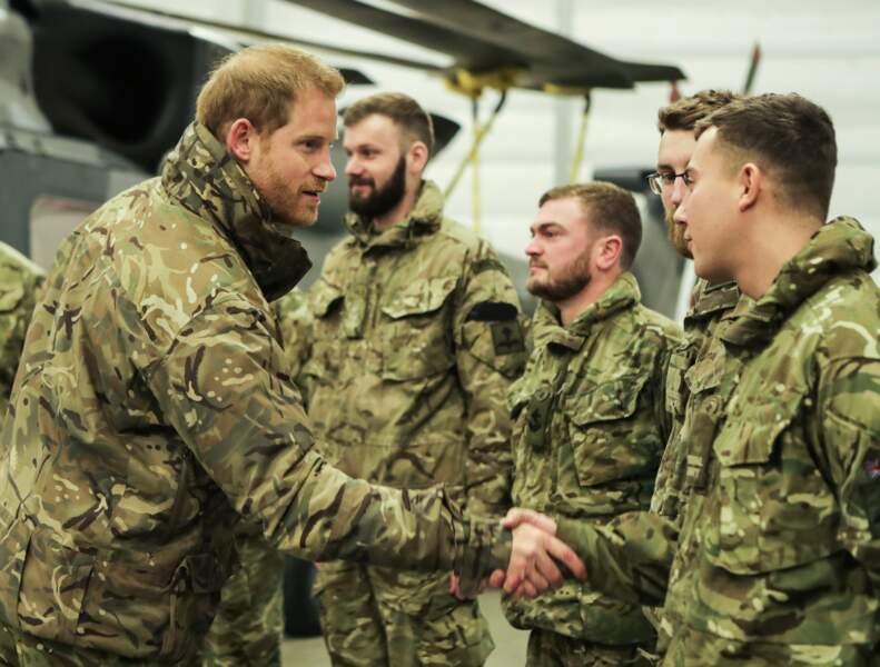Le prince Harry souriant lorsqu'il salue des membres des Royal Marines