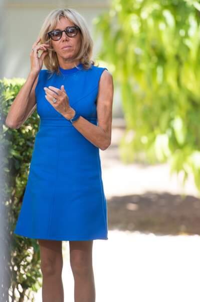 Brigitte Macron en petite robe cobalt et lunettes de soleil