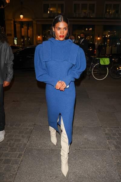 Tina Kunakey choisit une robe pull midi très cocooning avec sa paire de bottes blanches