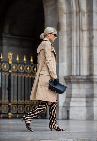 Caroline Daur choisit un simple trench classique avec sa paire de bottes branchée en zèbre