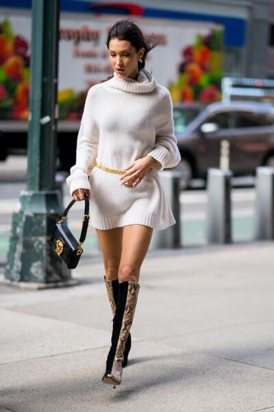 Bella Hadid matche sa paire de bottes bi matière avec une simple robe pull ceinturée