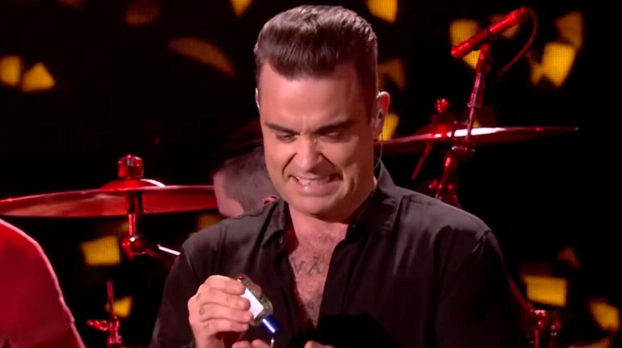 VIDEO Robbie Williams: dégoûté d'avoir touché ses fans, il se désinfecte sur scène