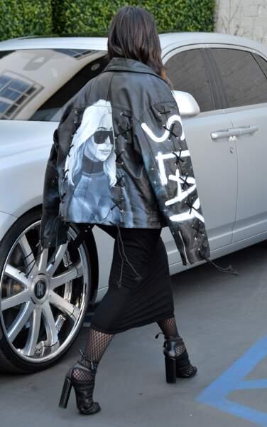 Kim Kardashian avec son portrait dans le dos. Au cas où on la reconnaitrait pas.