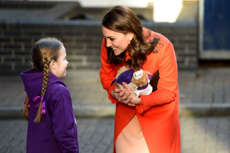 Kate Middleton, en rouge, mais sans sa bague de fiançailles lors de sa visite de l'hôpital de Great Ormond