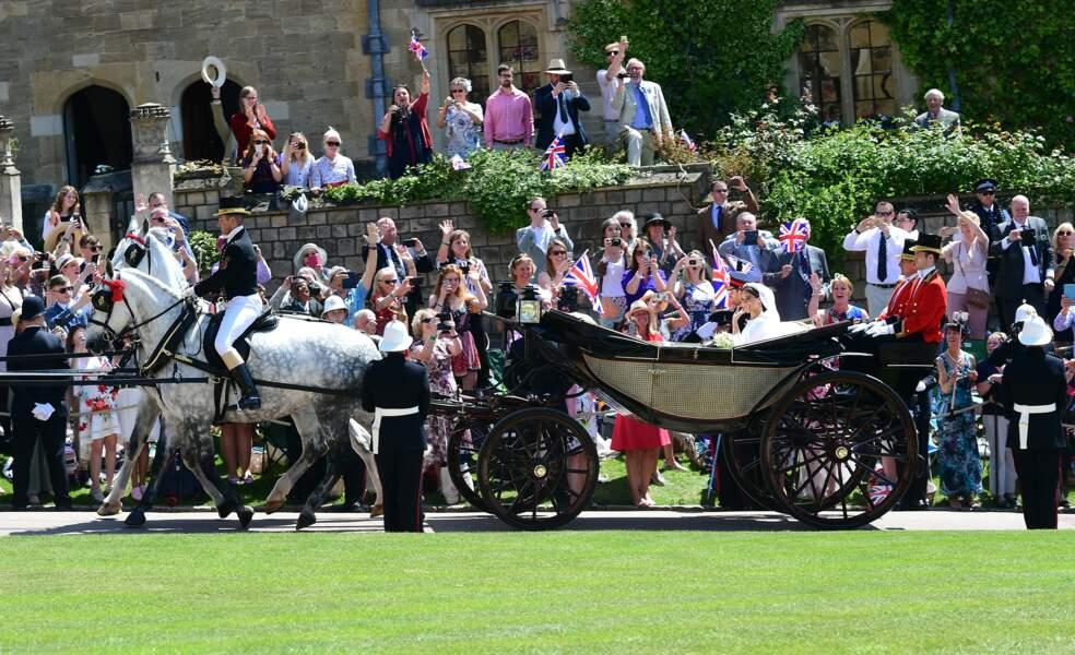 Le prince Harry et Meghan Markle saluant la foule